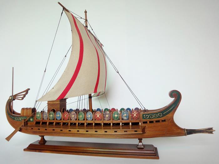 古罗马战船 该船模参照意大利古罗马博物馆中公元前50年浮雕原型,按原船风貌采用原始手工制作工艺按比例微缩复制而成,展现了早期古战舰的历史风姿。内部结构包括主、副龙骨,甲板及船板,采用优质香樟木、花梨木,船体表面及所有木制辅件采用红樱桃木。 长:98cm 宽:40cm 高:70cm